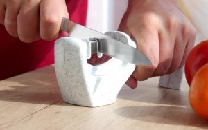 Manual sharpening of a knife in a sharpener in a kitchen