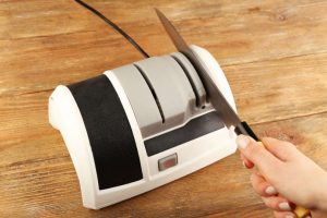 Sharpening knife with electric knife sharpener on wooden background