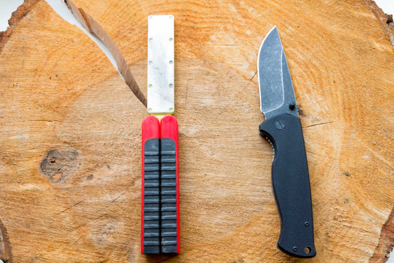 Set out a pocket knife and a pocket knife sharpener on a board