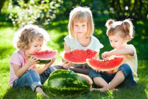 Group of happy children eating watermelon