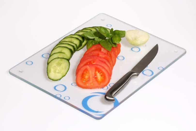 Sliced cucumbers, onions, tomatoes on a glass cutting board