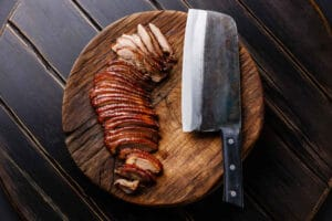Sliced Peking Duck and Chinese cleaver on cutting board on black wooden background