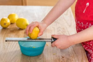 Little girl grating zest of organic lemon on kitchen table