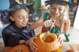 Kids preparing pumpkin for Halloween with their knife