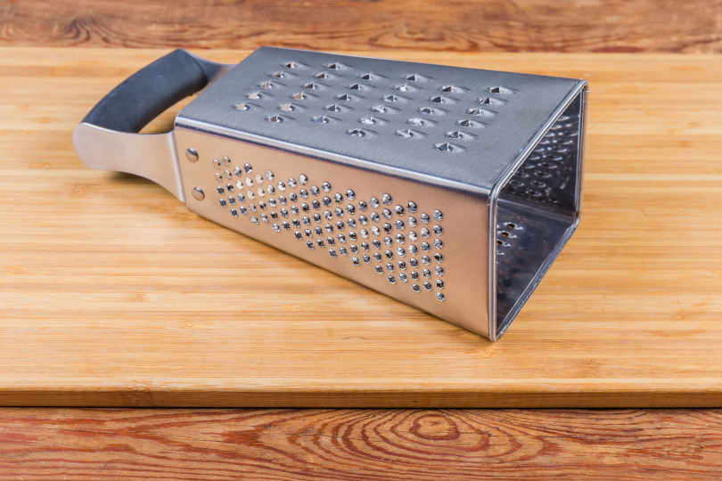 Stainless steel four-sided grater lies on wooden cutting board