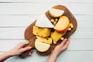 Hands and assorted cheese on wooden cheese board