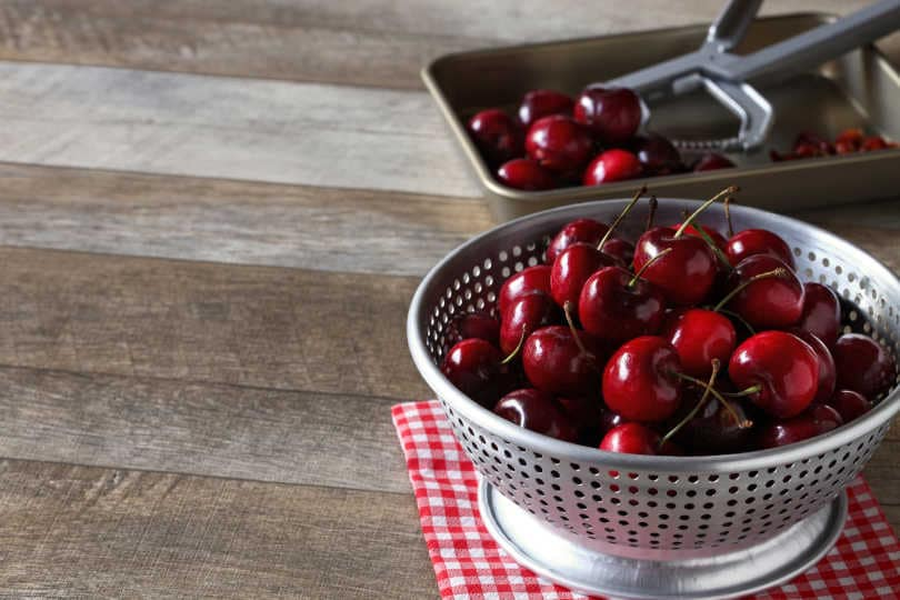 Removing pits from cherries in colander
