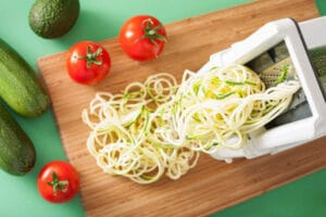 Spiralizing raw vegetable with spiralizer on a board