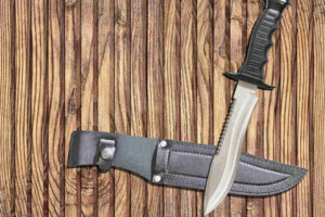 Bowie Knife with black leather knife guard on knotted pinewood