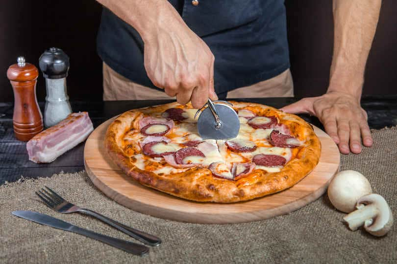 Cutting spicy pizza with salami, meat, ham, sausage, peppers, mushrooms, tomato, cheese with a pizza cutter on a wooden board on a black background