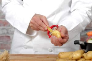 Hands of a man peeling potato with red peeler