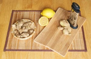 Ginger, lemon and grater composition on a board