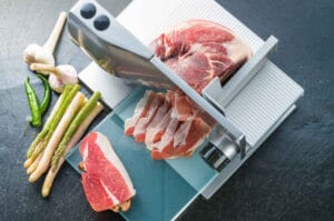 Slicing meat with a meat slicer on a table