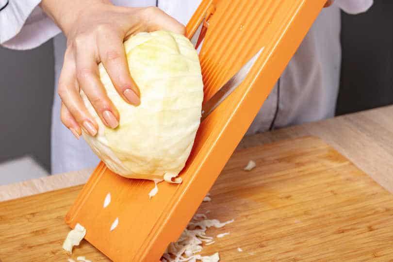 Slicing cabbage on shredder, preparation for cooking
