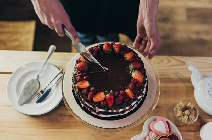 Woman cutting chocolate cake with cake knife