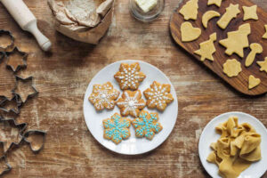 Flat lay with Christmas cookies on plate, ingredients and cookie cutters arranged on wooden tabletop