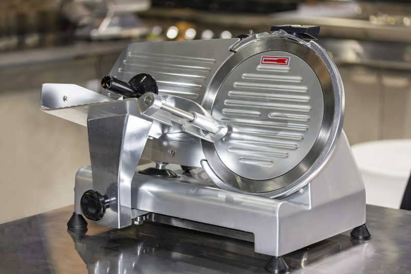 Electric semi automatic frozen meat slicer on the table