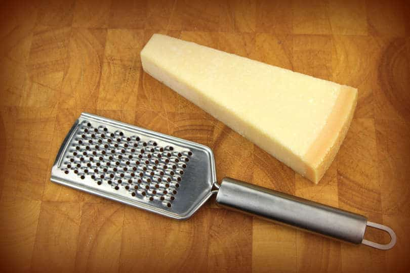 Parmesan cheese and grater on board