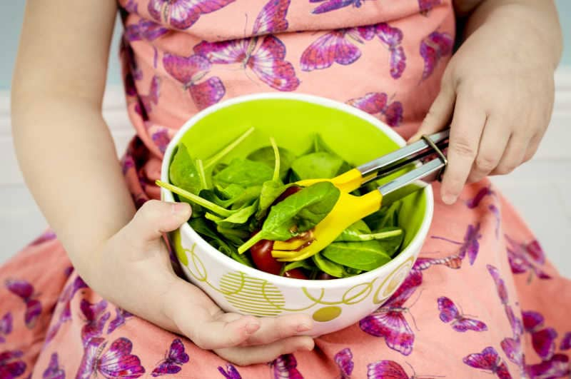 Child taking salad from bowl, using yellow salad tong