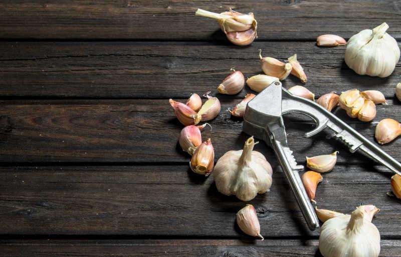 Garlic and garlic press. On wooden background