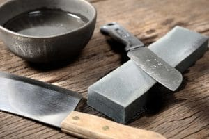 Knives, bowl and whetstone on a board to sharpen knives