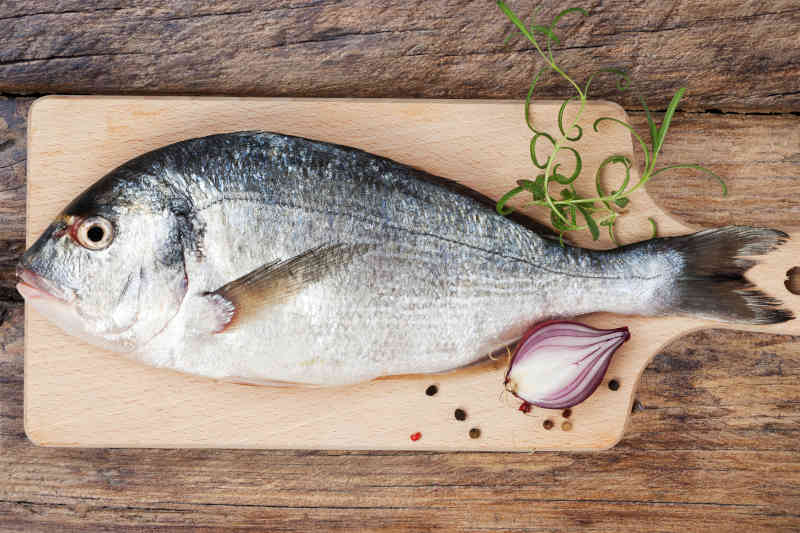 Delicious fresh sea bream fish on wooden kitchen board with onion, rosemary and colorful peppercorns on wooden background.