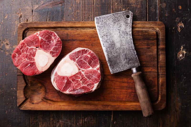 Raw fresh cross cut veal shank and meat cleaver on wooden cutting board