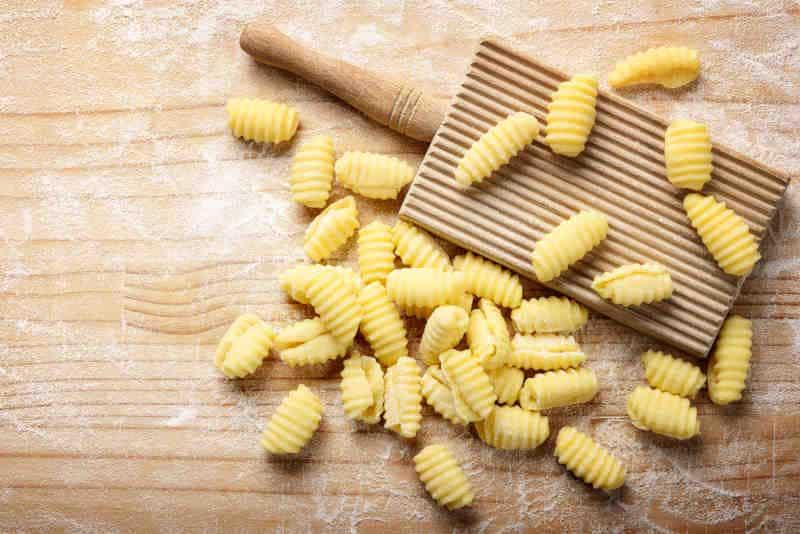 Durum wheat semolina gnocchi and gnocchi board on pastry board