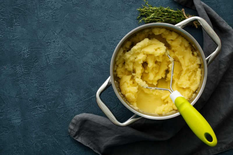 Mashed potatoes in bowl on a dark stone blue table, rosemary, napkin, top view