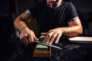 The man using whetstone to sharpening chef knife