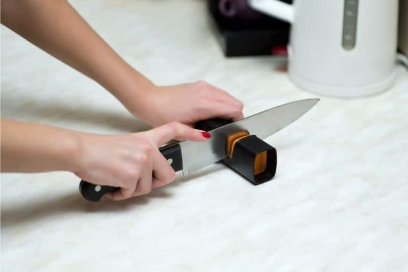 Woman sharpening a knife with a knife sharpener
