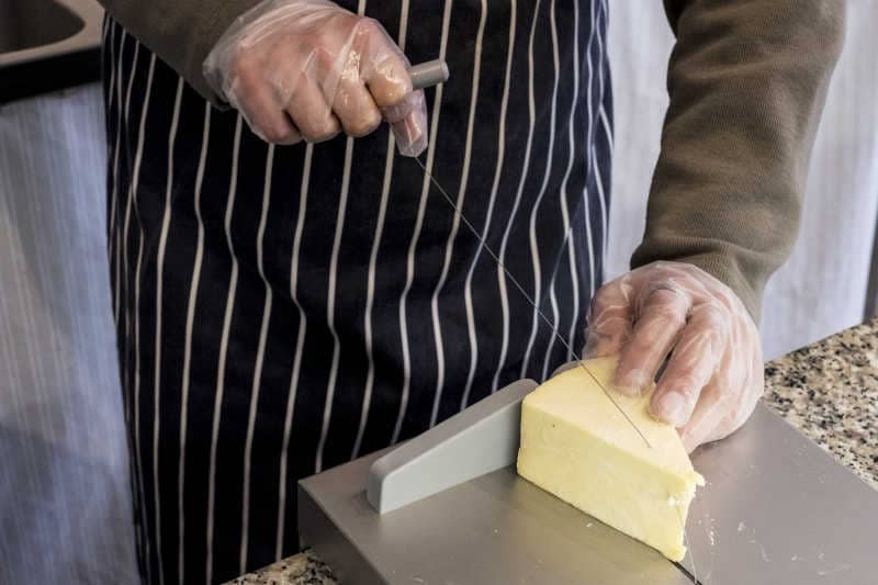 Man at counter in a delicatessen, slicing cheese with wire cheese slicer