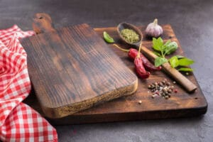 Cutting board and Spices. Hot peppers, Basil, Garlic and dried herbs