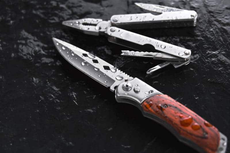 Folding knife and folding pliers on black background