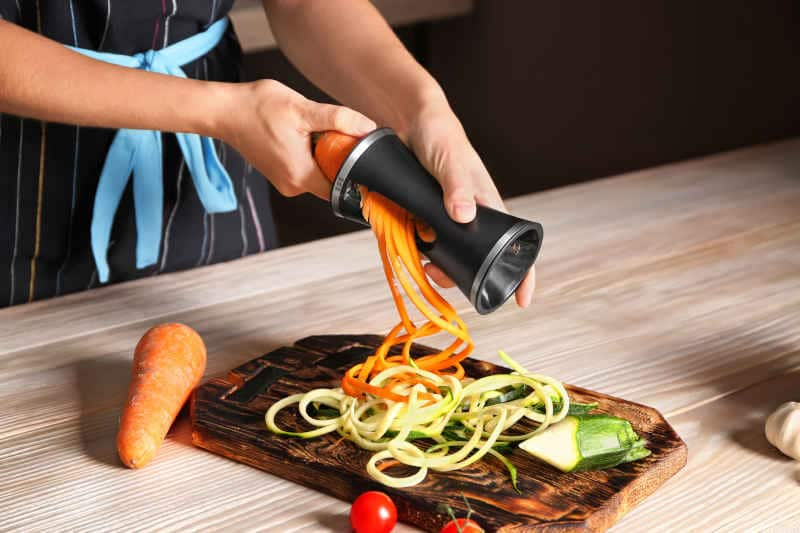 Woman making zucchini and carrot spaghetti with handheld spiralizer