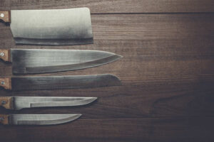 Five kitchen knives on the brown wooden background