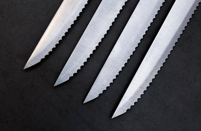 Serrated knives on the dark gray background