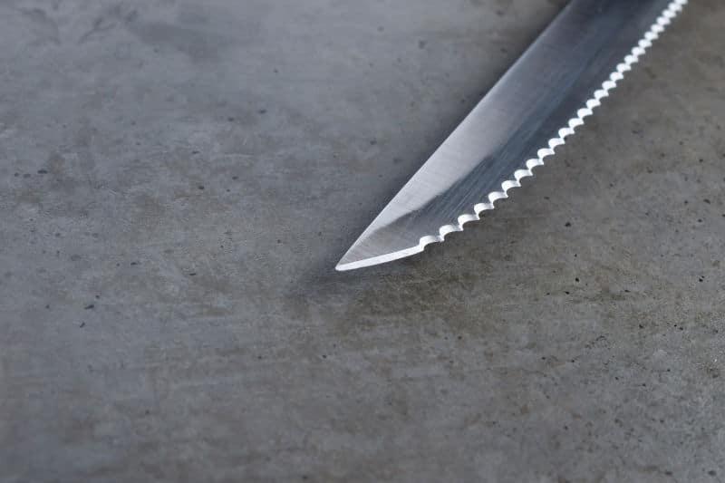 Sharp Serrated Paring Knife on a dark gray concrete table
