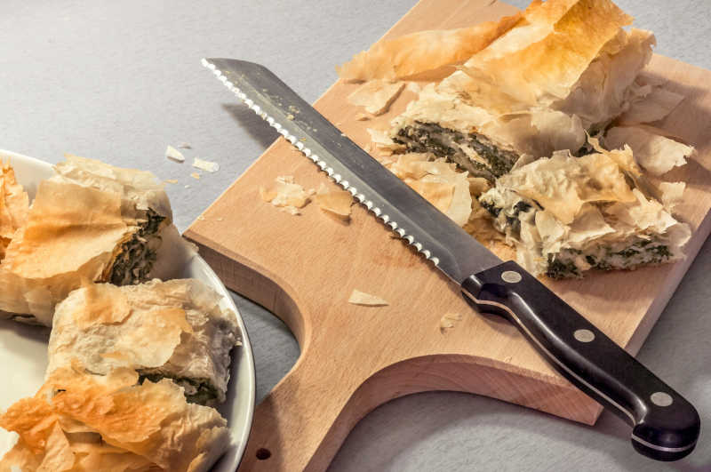 Freshly Baked Traditional Cheese Spinach Pie Roll Sliced With Serrated Knife on Wooden Cutting Board