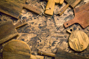 Various wooden cutting boards on wooden kitchen table