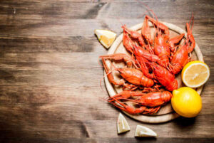 Boiled lobsters with slices of lemon on wooden board