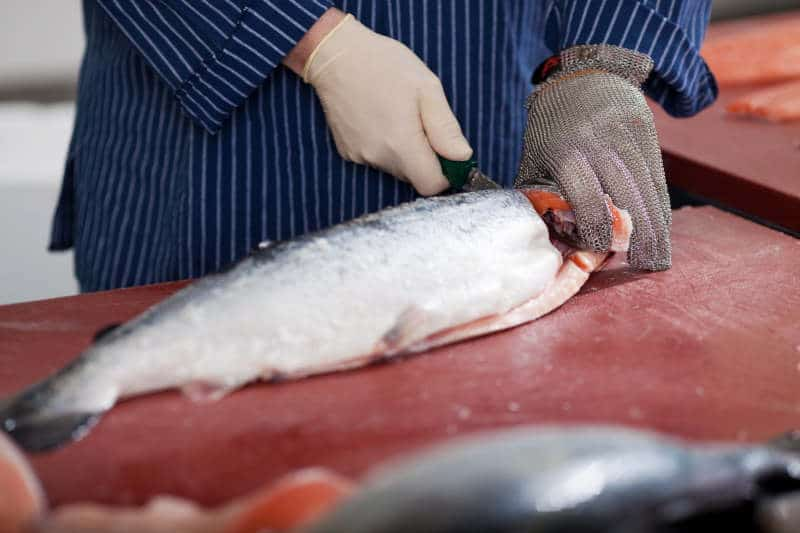 Man cutting salmon on a board with best folding fillet knife