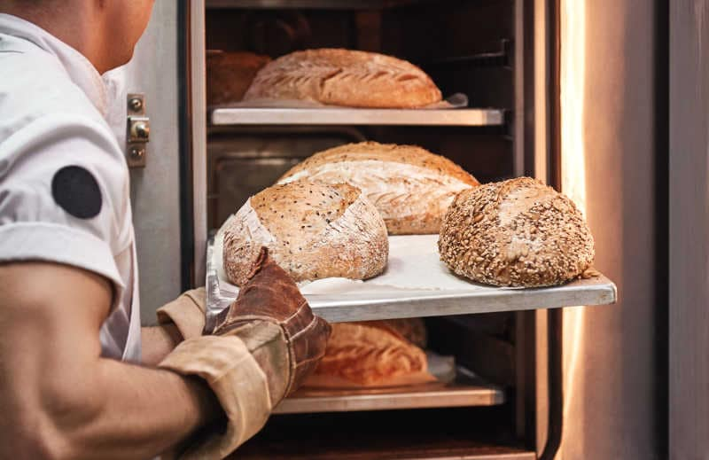 Baker's hands in working gloves taking out freshly baked bread from the oven at the kitchen.