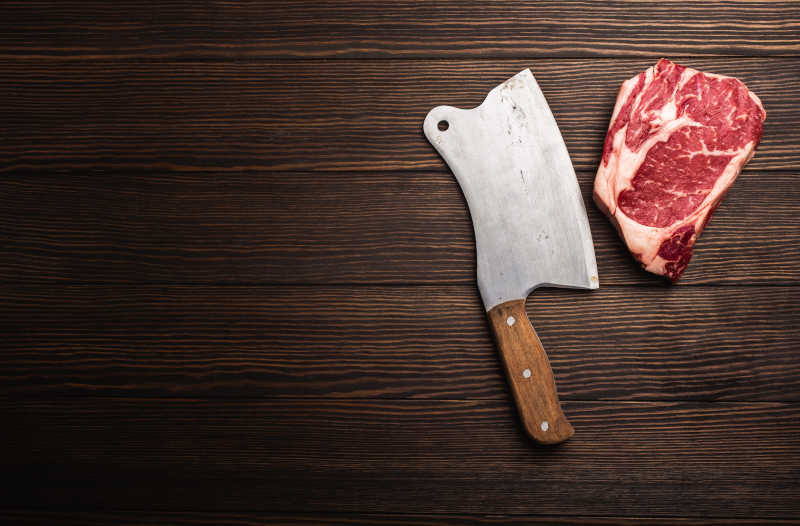 Raw fresh marbled meat steak Ribeye with rustic meat cleaver on wooden background