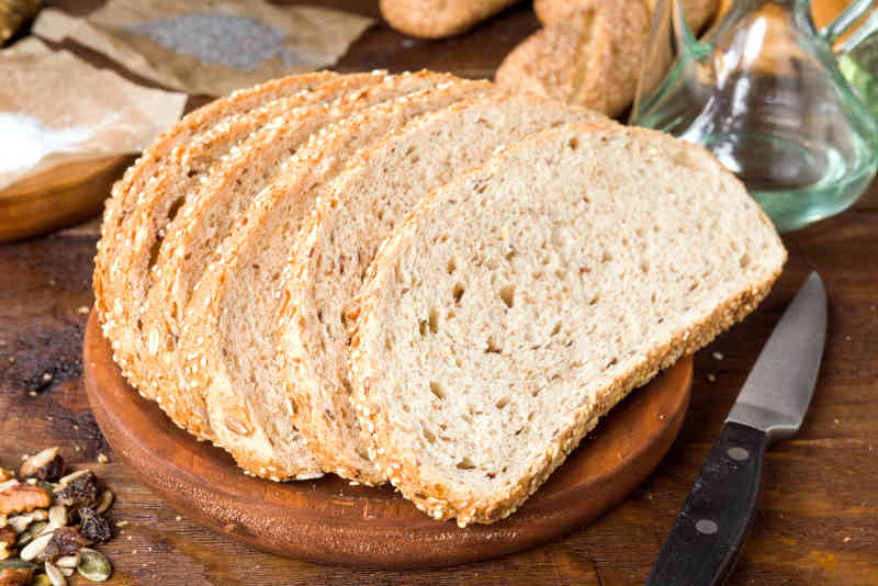 Home made seed bread slices on wooden board
