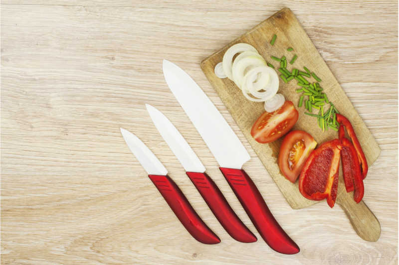 A set of paring knives and vegetable for salad on wooden board