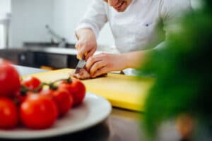 A young male chef cutting the meat in a professional kitchen
