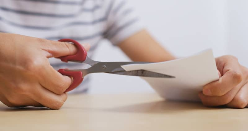 Man cutting paper by scissor