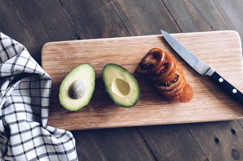 A sliced avocado and sliced tomato with a paring knife on a bamboo cutting board